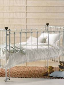 classic-baby-crib-with-metal-cage-white-sheets-small-dolls-and-rug